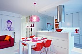 Red shell chairs around dining table against white kitchen counter in open-plan interior