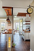 Open-plan interior with counter in foreground, kitchen with vintage station clock and lounge area with tall, lattice windows in background
