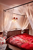 Four-poster bed with curved, metal headboard, transparent canopy and red, satin bed linen