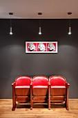 Rote Retro-Kinostühle vor dunkelgrauer Wand mit Andy Warhol Pop-Art Bild und Designer Pendelleuchten