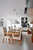 Set dining table, pale, upholstered chairs and pendant lamps with white lampshades in open-plan interior
