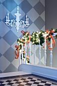 Weihnachtlich dekoriertes Treppengeländer, Wand im Schachbrettmuster mit Kerzenleuchter-Silhoutte