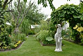 Vintage stone statue in ancient Greek style in garden