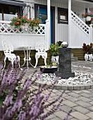 Ziersäule mit Edelstahl Kugel in kreisförmiger Einfassung, im Hintergrund weisse gusseieserne Gartenstühle mit Tisch, auf Terrasse eines weissen Holzhauses
