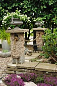 Two vintage urns of white-flowering plants on plinths connected by rope and low stone walls in garden