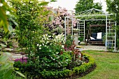Round bed edged by low hedge in garden in front of garden swing in metal pergola