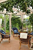 Wicker chairs with blue cushions on pale terracotta floor tiles in conservatory with view of garden