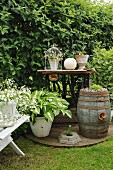 Nostalgic arrangement of planted, rustic barrel and ornaments on vintage sewing machine table in corner of garden