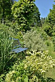 Light blue, vintage-style garden bench in summery gardens