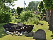 Traditional wooden rowing boat resting on rocks in summer garden