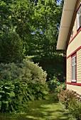 Sonnenbeschienene Fassade eines Holzhauses mit grünem Garten am Waldrand