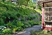 Geschwungener Gartenweg zwischen Hang und Landhaus