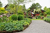 Gravel path lined by lush herbaceous borders leading to house and summer house