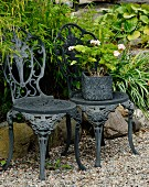 Ornate, antique, metal garden chairs and pink geranium in square pot with embossed pattern