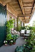 Balkon vor Loft mit verwittertem Charme, gemütlicher Sitzplatz mit Rattansesseln und beranktem Geländer