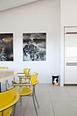 Gelbe Retro Stühle um Tisch, im Hintergrund Bilder an Wand, in modernem Ambiente mit Fliesenboden