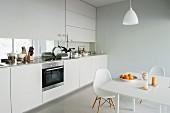 Essplatz mit Klassikermöbel in Weiss gegenüber moderne Küchenzeile am Fenster, mit integriertem Sichtschutz