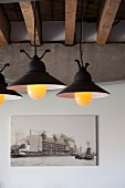 Beleuchtete Vintage Pendelleuchten unter sichtbaren rustikalen Balken, Betonträger und Fotografie in Loftwohnung