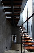 Staircase made from delicate steel structure and wooden treads next to glass façade