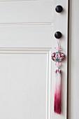 Ethnic-style pendant with tassel on doorknob of interior door