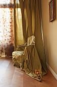 Eingewickelter und verschnürter Sessel vor bodenlangem Vorhang aus gleichem Stoff in Zimmerecke
