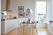Set table and modern chairs below designer pendant lamp; island counter below extractor hood
