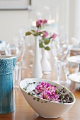 White china bowl of flowers on set table