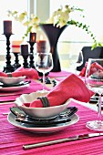 Place settings with hot pink linen napkins and place mats on festive table