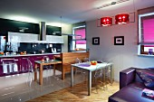 Open-plan interior; dining area with Ghost chairs, wooden counter and extendable kitchen table, modern fitted kitchen with purple and black accents