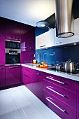 Modern fitted kitchen with purple fronts and stainless steel extractor hood