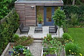 Raised beds in front of outdoor furniture on modern terrace with summer house