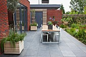Table and chairs on terrace with grey floor tiles adjoining modern, brick extension