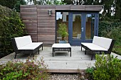 Outdoor furniture with dark frames and white seat cushions on terrace adjoining contemporary summer house
