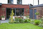 Blick vom Garten, über blühende Blumen im Beet und Terrasse, auf modernen Anbau aus Ziegel
