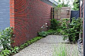 Narrow flowerbed and gravel area next to brick wall with bicycle stand in foreground