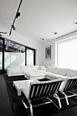 White lounge seating around low coffee table below black track lighting system with spotlights