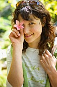 Young woman holding pink flower in front of eye