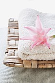 White towel and pink flower on wicker tray