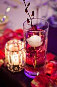 Detail of wedding table with floating candle and orchid in glass of water