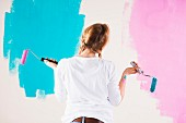 Young woman holding paint rollers considering two different wall paints