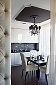 Chandelier hanging from ceiling panel in elegant kitchen-dining room; edge of button-tufted partition in foreground