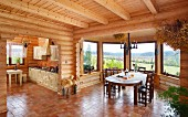 Spacious interior with dining area in window bay and open-plan kitchen in log cabin