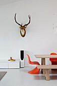 Teilweise sichtbarer Esstisch und Klassikerstuhl in Orange, vor Wand mit Hirschtrophäe