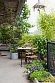 Terrasse eines Lofts mit Pflanzen und Bäumen, dazwischen kleiner Sitzplatz
