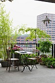 Old bistro table and simple chairs in front of planters on loft apartment terrace; view of city over balustrade