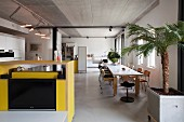 Yellow kitchen counter, long dining table and chairs in loft apartment