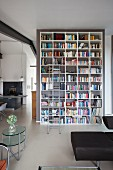 Tall bookcase with ladder against partition and retro side table in loft apartment interior