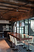Elegant wooden counter and white swivel bar stools below pendant lamps and spotlights attached to power rail on wood-beamed ceiling; floor-to-ceiling windows with louver blinds