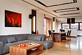 Lounge area with grey corner sofa and walnut coffee table in front of dining area in loft-style interior