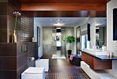 Elegantes Designerbad - Massgefertigter Waschtisch, gegenüber Sanitärmöbel an braun gefliester Wand, im Hintergrund Duschbereich
